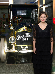 Besser Museum staff member standing next to an Alpena Flyer automobile