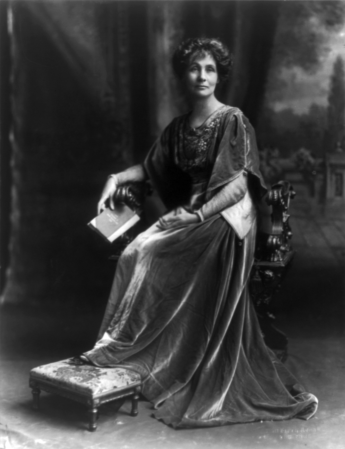Emmeline Pankhurst posed portrait sitting in chair with book