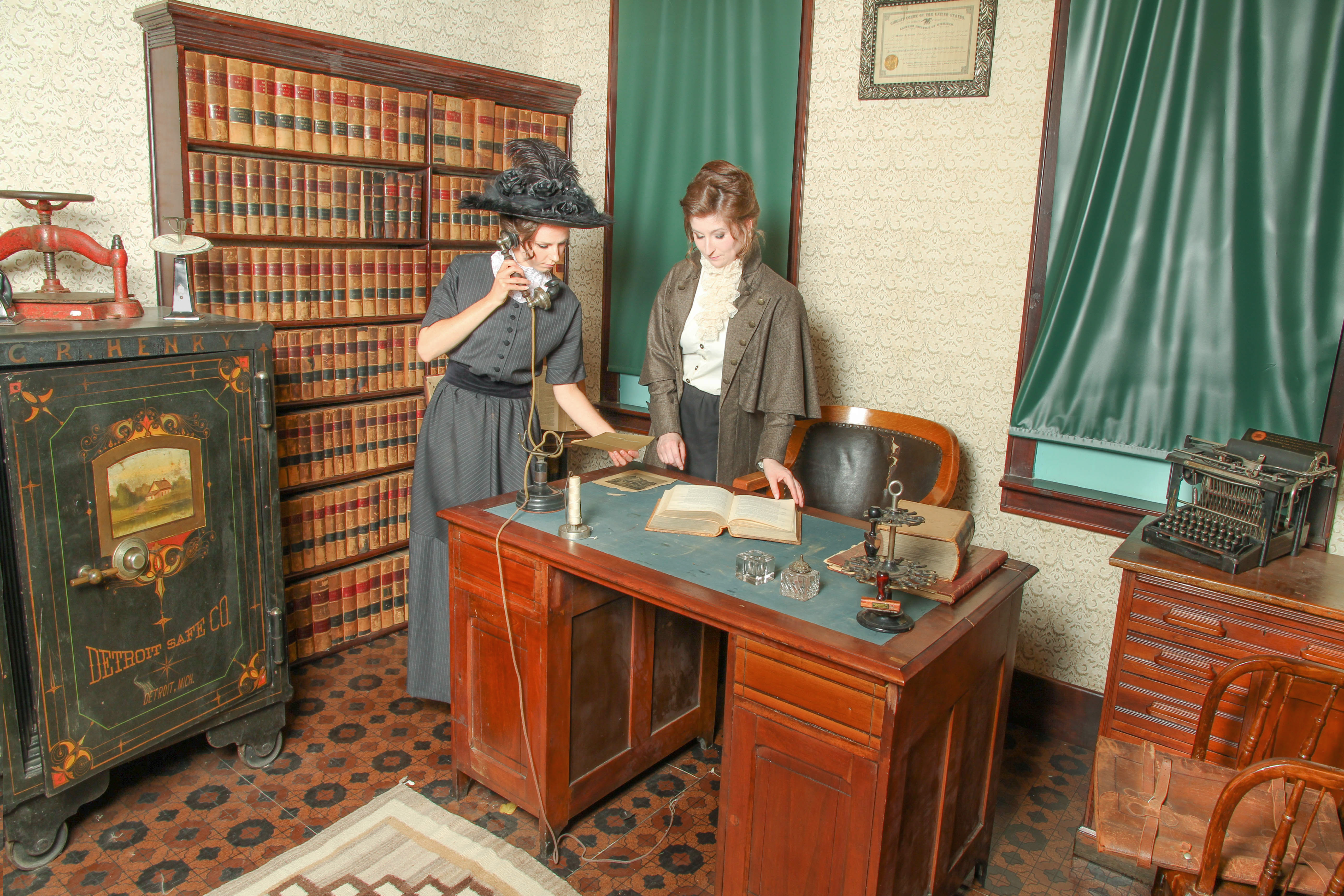 models in Edwardian clothing making a call from the lawyer's desk