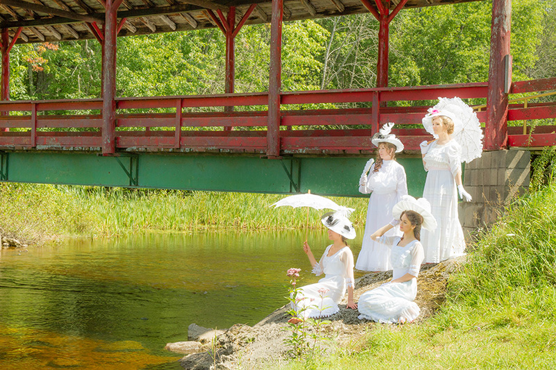 4 models in white Edwardian clothes on the bans of the Trout River
