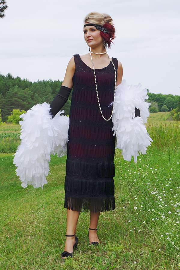 Blonde woman wearing black flapper style dress with a large white boa standing in a field.
