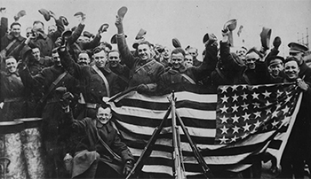 Soldiers pose with American flag at the end of World War I.