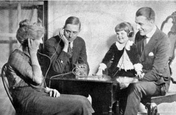 People sharing headphones to a crystal radio, c. 1920