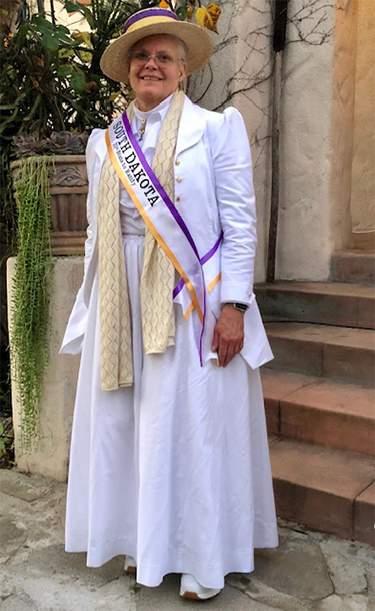 Ellen Snortland wearing Hyacinthe in white with a suffrage sash