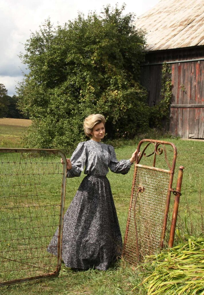 Woman in pioneer clothing standing in a field wearing a long-sleeved blue top and long blue skirt.