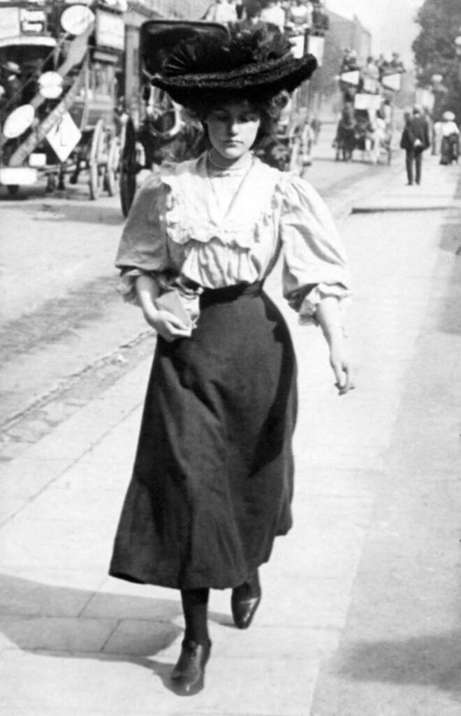 Black and white photograph of Edwardian woman in long black skirt and large black hat